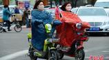 """內蒙古寒潮來襲 騎電動車的行人穿上""""棉衣""""出行"""