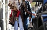 米歇爾·亨澤爾長皮衣配白褲御姐範訪問幼兒園 單臂抱娃無損女王氣場