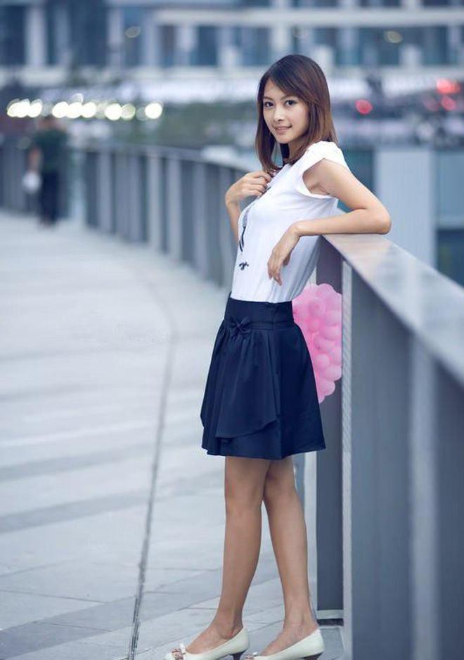 小智圖說-拿粉色氣球穿短衫和黑短裙在路旁的護欄旁休息的美女!