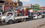 柬埔寨首都金邊街頭實拍:卡車車斗站滿乘客,還有人坐在車廂頂上