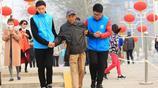 玉淵潭櫻花節:大學生志願者攙扶老人過拱橋,服務真周到