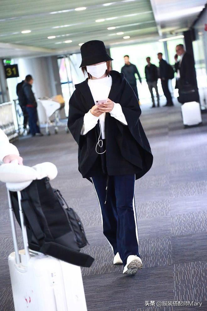 """謝娜著氣質純色斗篷現身機場,低頭玩手機變身""""低頭族"""""""