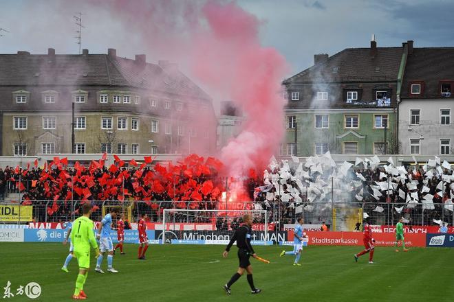 球員踢著足球突然觀眾席上著火,球迷淡定揮旗加油!
