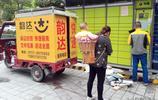 湖北宜昌:街拍拾趣 奶奶揹著孩子觀看快遞員投送快遞