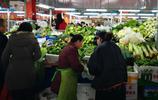 除夕上午,內蒙古包頭一市場蔬菜堆積如山,老闆站在高臺上賣菜