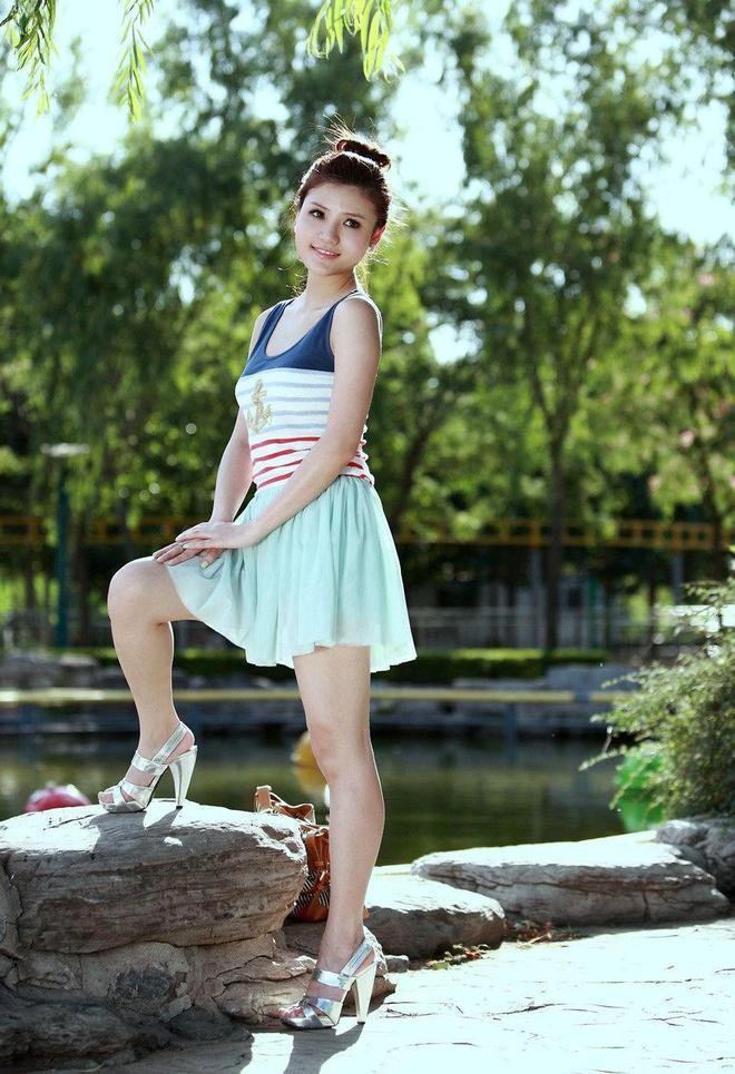 小智圖說-穿彩色條紋裙身材高挑氣質的美女在湖邊石上坐著休息!