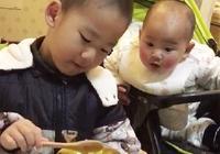 1歲弟弟看哥哥吃飯,饞的眼珠子快瞪出來了,弟弟:給我留點