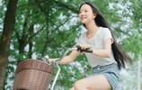 小智圖說-晴朗天氣,穿短衫騎著單車到戶外遊玩的長髮清麗女孩!